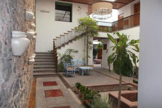 La Hija del Alfarero: Uno de los patios del hotel y escalera hacia planta alta.