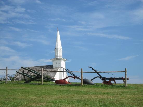 Iona, Canadá: The  Church with different plows in the foreground
