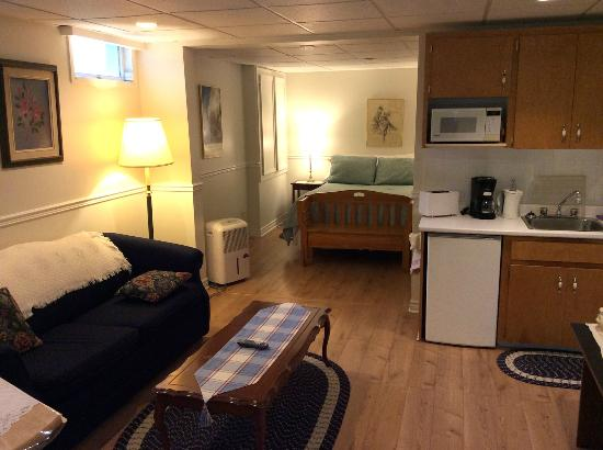 The Worn Doorstep: Living room area with kitchenette and TV