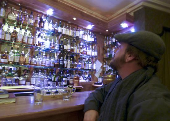 Poppies Hotel & Restaurant : my husband admiring the whisky selection