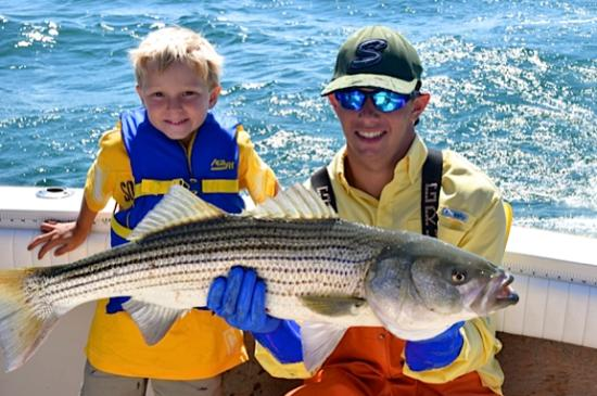 Fishtale Sportfishing: 1st mate Finn, with happy angler Cy.