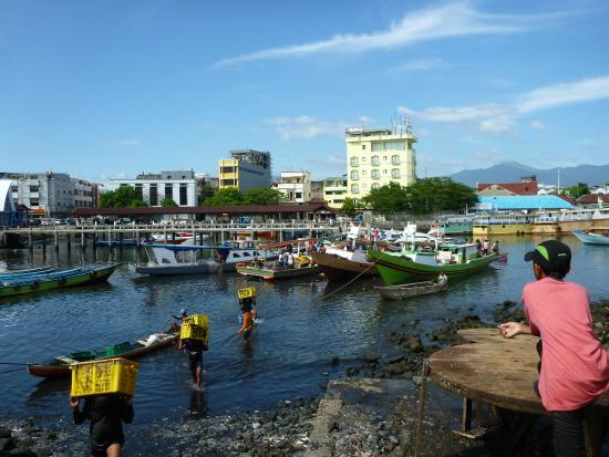 view of the yellow Celebes Hotel across Manado Harbour