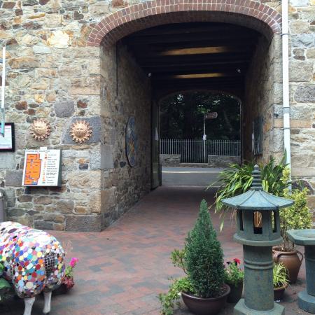 Devon Guild of Craftsmen: Back end of arty pig in front of wagon entrance.
