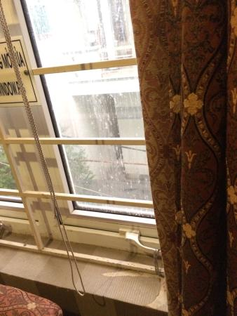 Royal Hotel Danang: A lot of paper textures of wall are split from the wall. The window glass is stained and dirty.