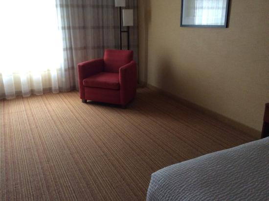Courtyard by Marriott Traverse City: Random chair surrounded by empty space.Could they at least give a footrest?