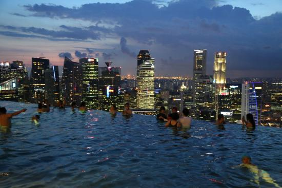 View from the infinity pool at dusk picture of marina bay sands singapore tripadvisor for Marina bay sands swimming pool entrance fee