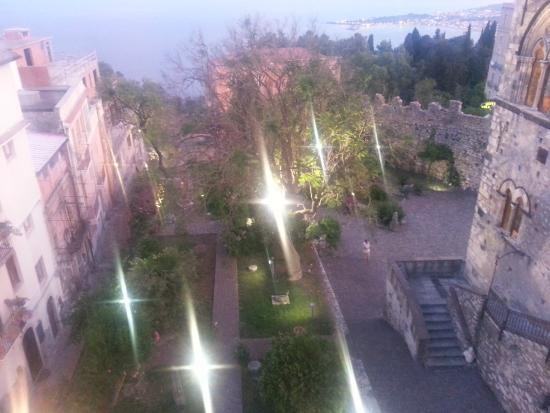 Hotel Del Corso: Night view of courtyard and sea from rooftop dining area