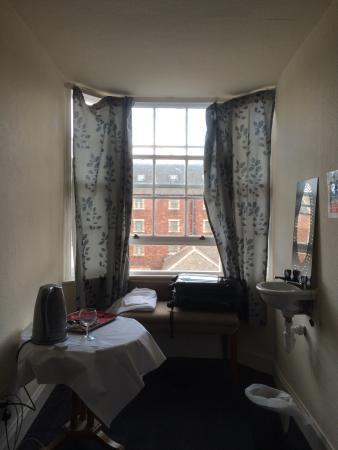 Abbot's House Hotel: Die Waschgelegenheit im Zimmer, Blick zum Fenster, 2. Fenster, Bett und Tür
