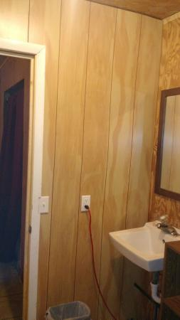 Riverdale Resort : Bathroom. That red chord is the power for the hot water heater, which goes down and thru the wal