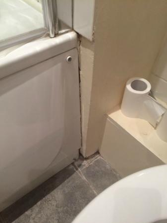Nell Gwynn House Apartments: Missing toilet paper holder and improperly sealed bath tub