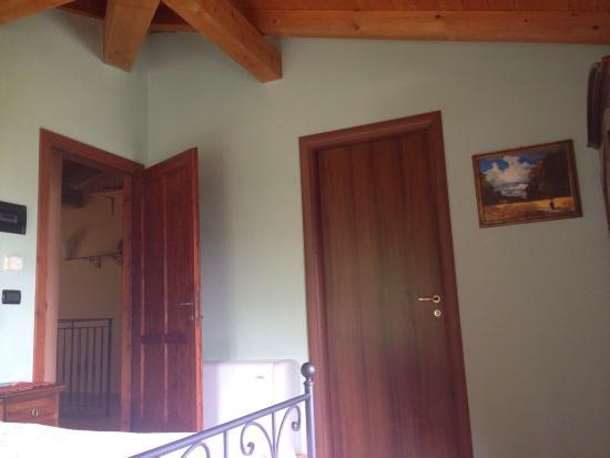 Camera D Angolo Con Travi A Vista E Letto In Ferro Battuto Photo