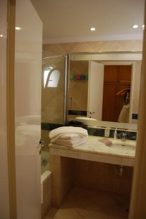 Mitsis Rinela Beach Resort & Spa: Badkamer met lavabo, wc en bad met ...