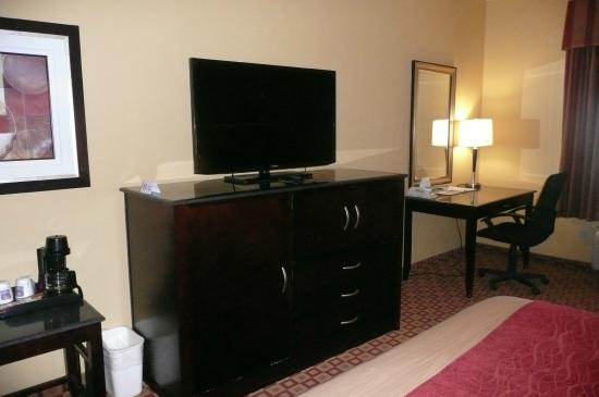 Comfort Inn & Suites: Cabinet with fridge, microwave, and drawers, plus desk