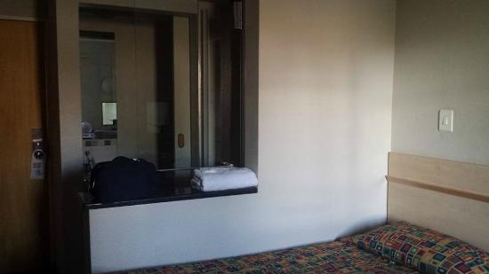 Road Lodge Rivonia: stanza da letto, doccia dietro alla parete bianca affiancata al letto, bagno/sgabuzzino