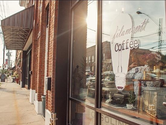photo of coffee shop from Mebane's downtown sidewalk with sun reflecting