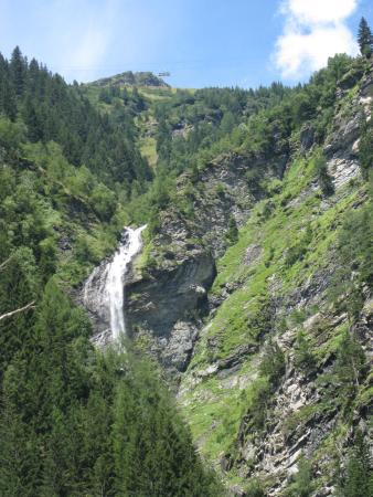 Mallnitz, Austria: Над водопадом три кабинки везут туристов на пик Анкогель (Ankogel)