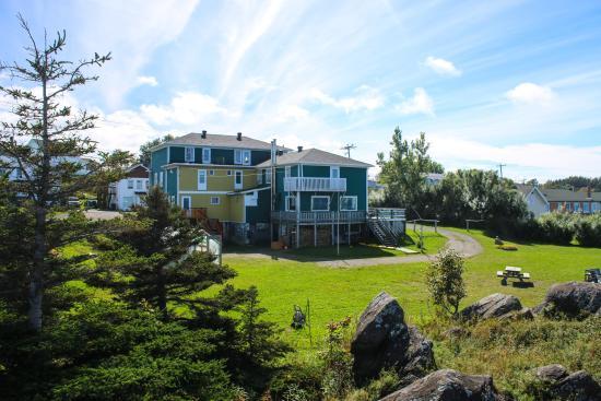 Auberge de Jeunesse du Manoir des Sapins : Le Manoir vu des rochers au bord de l'eau