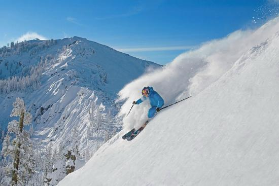 Norden, CA: Olympian & resort ambassador Daroh Rahlves skiing with the famed Palisades behind him