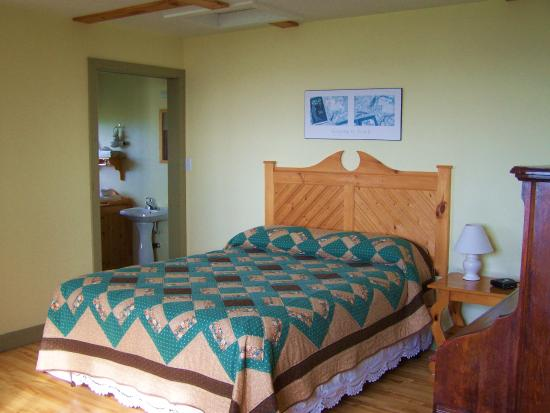 Cape Anguille Lighthouse Inn: view of bed with bathroom behind