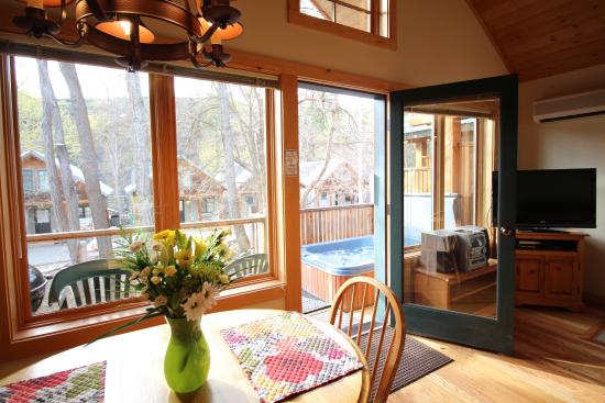 River's Edge Resort: Cozy Cabin Dining Area & View Of Hot Tub on Deck