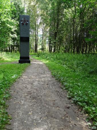 Danilov, Russland: дорога к храму идет через лес и рядом памятник