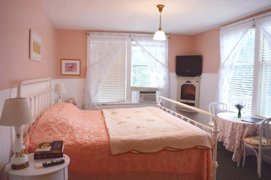 Room 214 -- A pink-themed bedroom with a king bed, cozy ...