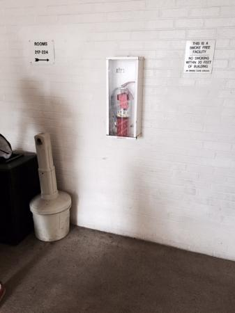 """Motel 6 Martinsburg: Irony?? Cigarette disposal right next to building and """"no smoking within 20 feet of building"""" si"""