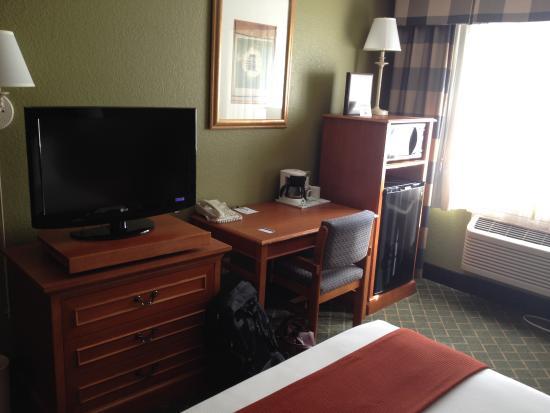 GuestHouse Inn & Suites Poulsbo: Blick auf TV, Schreibtisch und Kühlschrank mit Mikrowelle