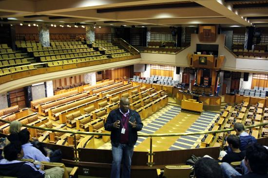 Parliament of the Republic of South Africa: A tour guide engaging with a tour group in the National Assembly Chamber.