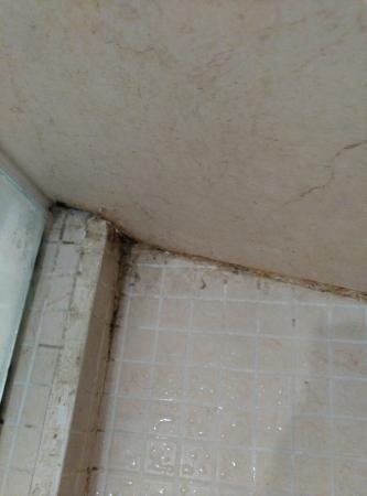 Hotel Santa Rita: Ducha sucia, suelo bajo mesita con cosas, suciedad en grifo y cama mal hecha al quitar la colcha