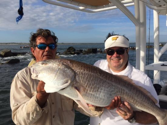 Red fish at the new smyrna beach jetty picture of the for Deep sea fishing new smyrna beach