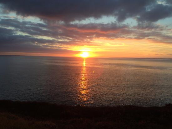 ‪‪Gunwalloe‬, UK: Sunset over the sea, seen from the Halzephron House garden.‬