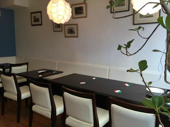 Cantinetta Adorno: 白壁と木目のテーブルの明るい店内