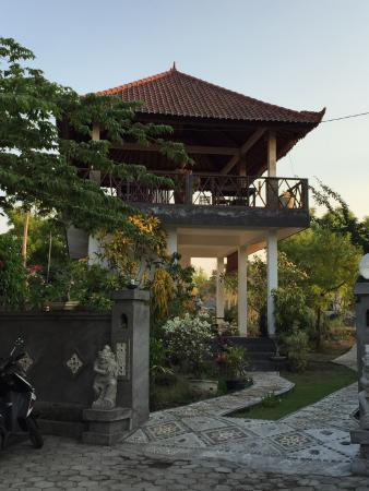 An elevated open air  pavilion, a simple garden setting, a magnificent view of Mt Agung, grilled