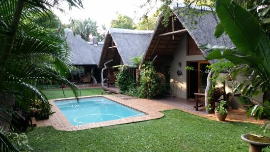 Mhlati Guest Cottages: View across lawns and pool to the Leopard Cottage and lapa.