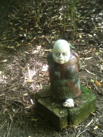 Normanville, France : Un moine de terre cuite sous un sois bois de bambou