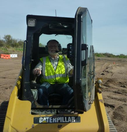 Hastings, MN: Man at the helm of a skid steer, his new favourite toy.
