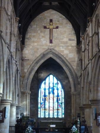 The pointed arch and ornate cross over the altar - Picture