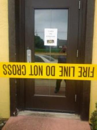 Romano's Macaroni Grill: Close-up of Fire Marshal tape at side door and notice of closure.