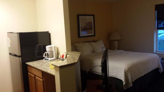 TownePlace Suites Milwaukee Brookfield: bed and full size fridge in room with side view of tv