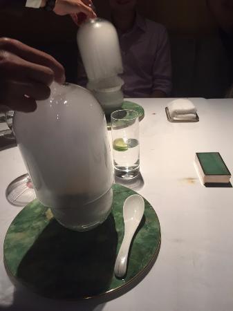 Mango dessert served under a misty glass dome