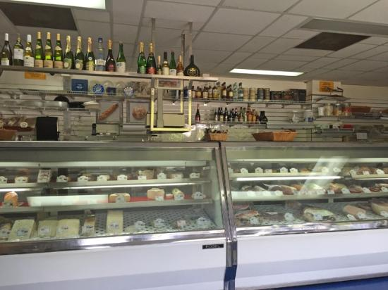 French Deli & Gourmet Shop : The cheese and meat counter with wine on the top shelf.