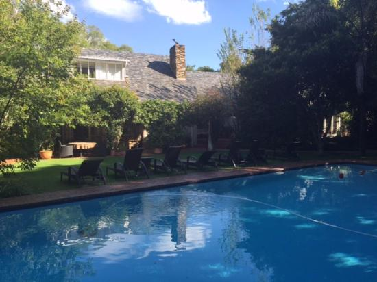 Melrose Place Guest Lodge : View of pool and main house from thatched cottage