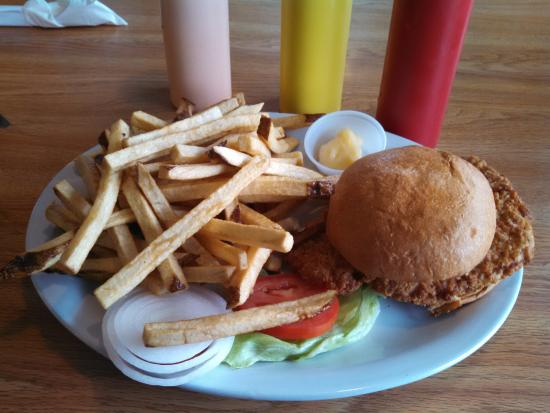 "Grumpy's Cafe: The ""Oink"", breaded pork chop on a bun with dressings, french fries, and applesauce (not in phot"