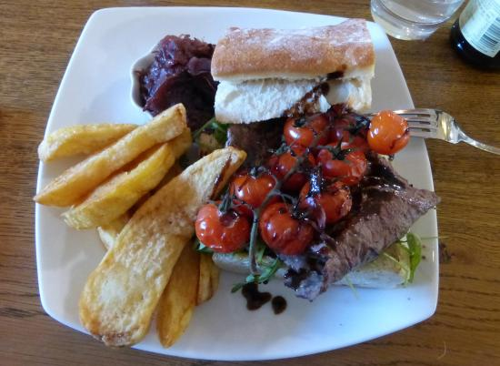 Snape, UK: Thinly sliced steak on ciabatta, roasted vine tomatoes, caramelised onions and  chips