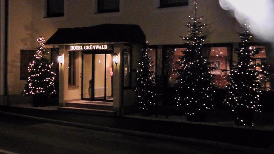 Hotel Grünwald Garni: View of the hotel entrance with the Christmas trees outside.