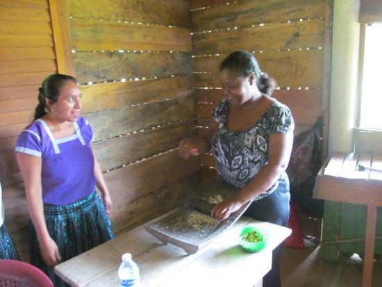 Punta Gorda, Belize: Garifuna friend trying corn grinding under Mayan guide supervision