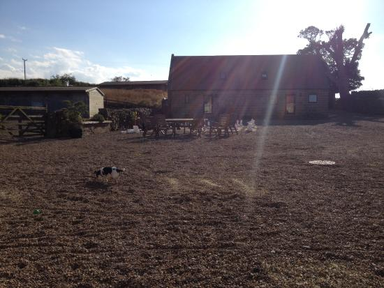 Fylingthorpe, UK: View across courtyard, giant chess, more tables, stables full of toys and bikes!