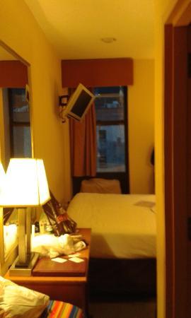 Econo Lodge Times Square: Litet rum mellan vägg o sänggavel yterst litet utrymme