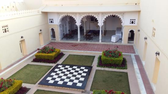 Chandeliered courtyard used for evening meals with local musicians playing in garden.